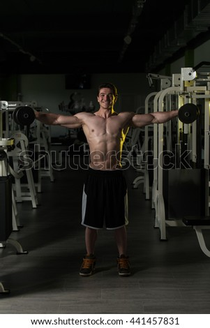 Young Man Exercising Shoulders With Dumbbells And Flexing Muscles - Muscular Athletic Bodybuilder Fitness Model Exercises - stock photo
