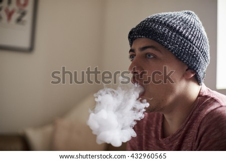 Young Man Exhaling Whilst Using Vapourizer - stock photo