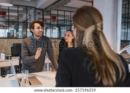 Young man explaining new business plan to coworkers during a meeting around a table in office. - stock photo