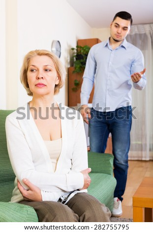 Young man explaining something to offended mature woman - stock photo
