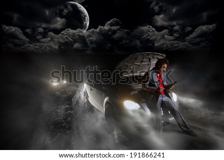 Young man exploring the map on tablet pc computer  in the middle of the trail in the night  - stock photo