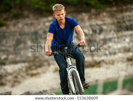 Young man extreme cyclist riding a bike in mountain - stock photo