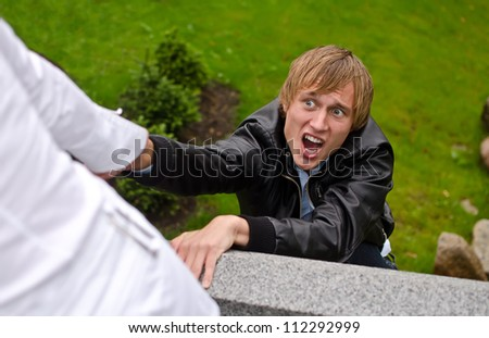 Young man falling down from the bridge - stock photo