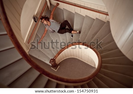 Young man falling down into the steep spiral staircase - stock photo