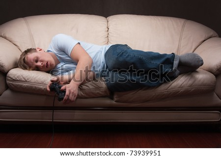 young man falls asleep while playing video games on gray background