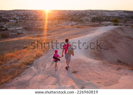 Young man father dad with little daughter kid child walking in valley and meeting sunset in Cappadocia Turkey - stock photo
