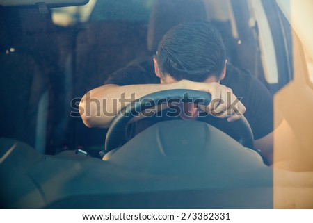 Young man feeling frustrated and upset and leaning on the steering wheel. Shot through the windshield - stock photo