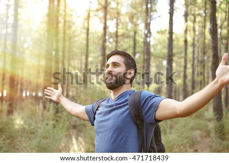 Young man feeling the energy of the forest with open arms in a plantation while wearing casual clothing and a backpack