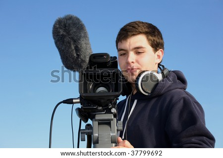 Young man filming video outside