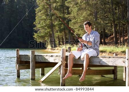 Young man fishing - stock photo
