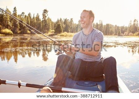 Young Man Fishing From Kayak On Lake - stock photo