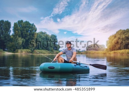 Young man fishing from the rubber boat on the pond