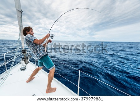 Young man fishing hard in open sea from sail boat - stock photo