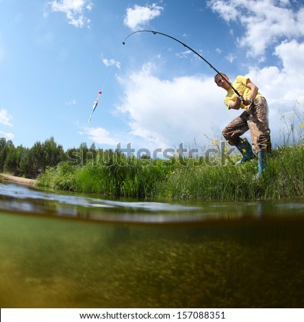 Young man fishing in a pond in a sunny day - stock photo
