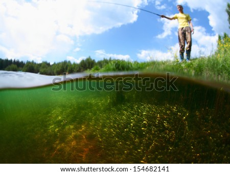 Young man fishing in a pond in a sunny day. Focus on the weed underwater - stock photo