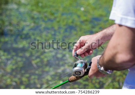 Young man fishing in pond, lake, closeup of fishing rod and reel.