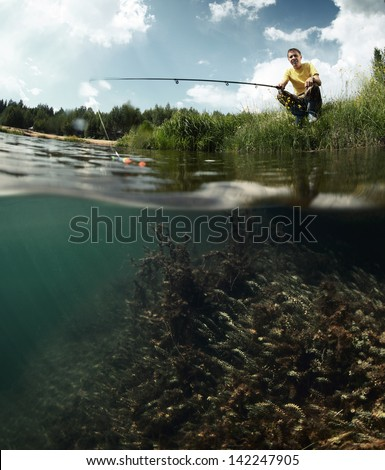 Young man fishing on a green pond's coast with underwater view of weed on a bottom - stock photo