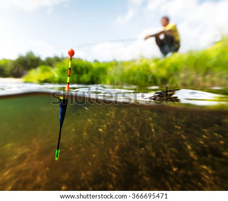 Young man fishing on a lake with underwater view of the bottom - stock photo
