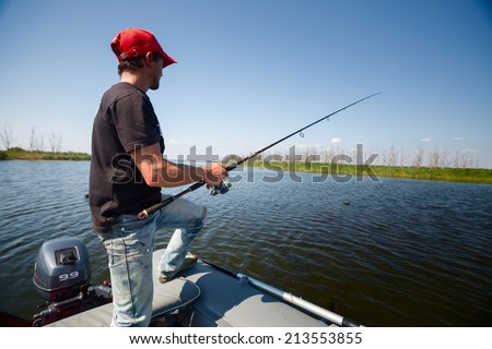 Young man fishing on a river from the boat at sunny day