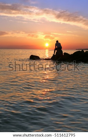 Young man fishing on a  seaside during beautiful sunset