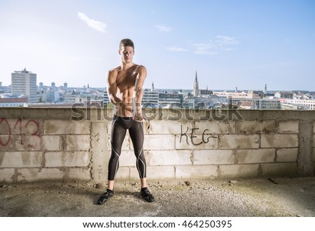 Young man fit stretching arm building outdoors model city background