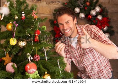 Young man fixing Christmas tree lights - stock photo