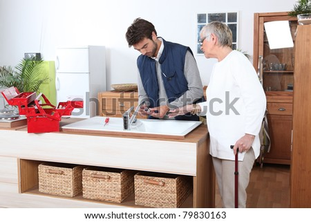 young man fixing faucet older woman - stock photo