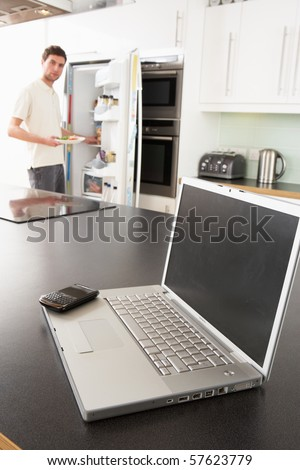 Young Man Fixing Snack In Kitchen With Laptop In Modern Kitchen - stock photo