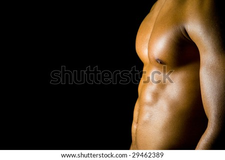 Young man flexing his abdominal muscles - stock photo