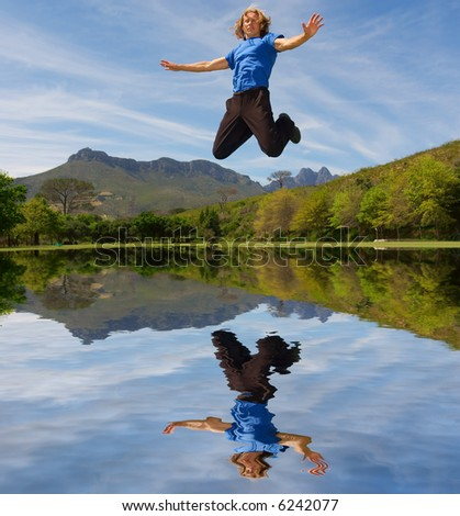 Young man flies above lake in misty majestic mountains. Shot in Coetzenburg, Stellenbosch, Western Cape, South Africa.