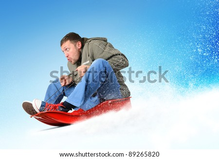 Young man flies on sled in the snow, concept winter sport - stock photo