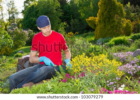 young man - florist-  working in garden - stock photo