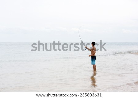 young man fly fishing on beach - stock photo