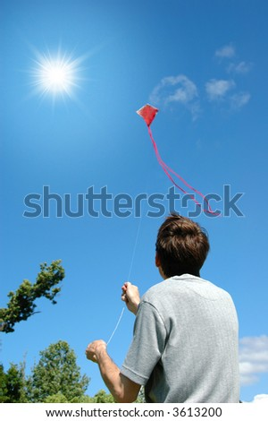 Young man flying a kite on a sunny day - stock photo