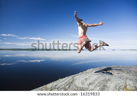 young man flying above a rock