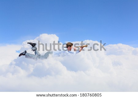 Young man flying high in sky and looking in spyglass - stock photo