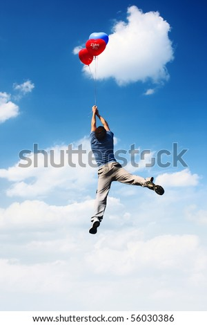 Young man flying in blue cloudy sky with colored balloons - stock photo