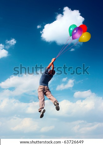 Young man flying in blue sky holding group of bright balloons - stock photo
