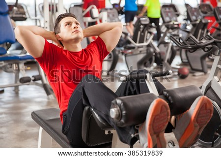 Young man focused on his workout and doing some crunches in a gym - stock photo