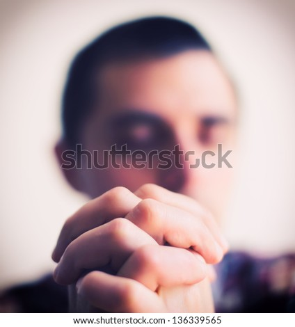 young man folded his hands together - stock photo