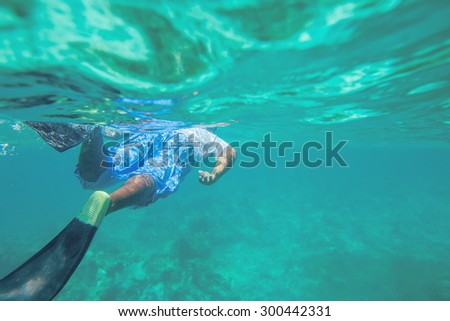 Young man free diving and snorkelling over a reef in the Caribbean Sea