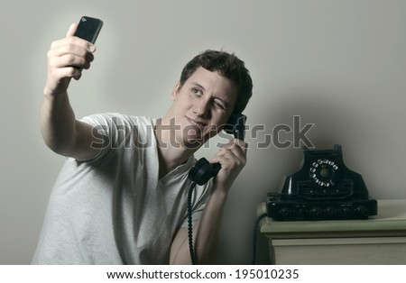 Young man Fun with Smartphone Photography and retro phone - stock photo