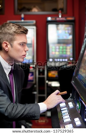 Young man gambling on the slot machine in casino - stock photo