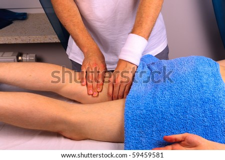 Young man gets thigh massage - stock photo