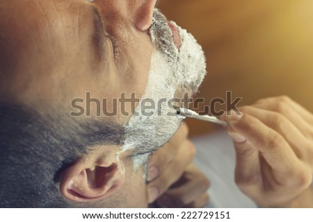 Young man getting an old-fashioned shave with straight razor. Closeup, retro styled imagery - stock photo