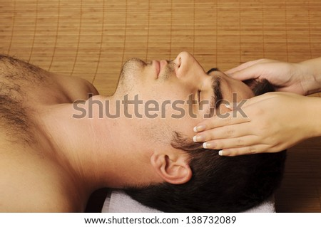 Young man getting face massage at spa
