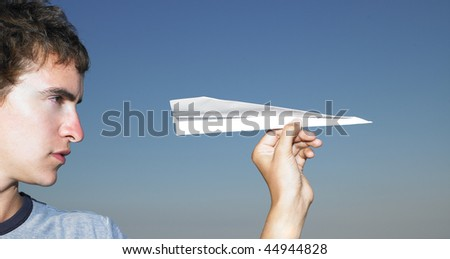 Young man getting ready to throw a paper airplane. Horizontal shot. - stock photo