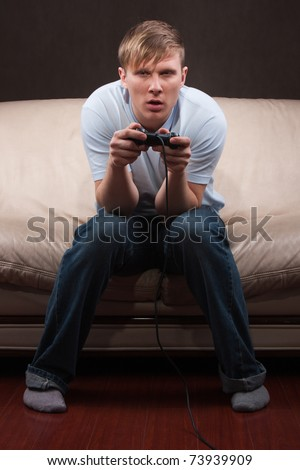 young man getting tired while playing video games on gray background - stock photo