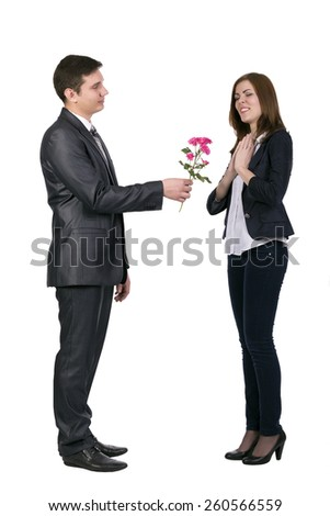 Young man gives a branch of flowers to beautiful lady. Full body portrait of two young people. Male passes flower to female. She expresses pleasure and delight. Official dress code,white background