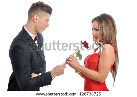 Young man gives a red rose to a young woman - stock photo